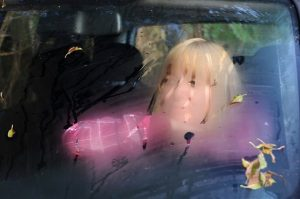 Blurry portrait of the middle-aged woman looking through the car fogged windshield